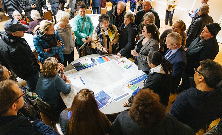 Image of community members standing around a table talking to Sound Transit staff at an open house earlier this year
