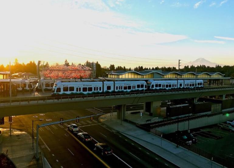 一列Link light Rail(轻轨)列车在高架轨道上行驶,背景是雷尼尔山 (Mt. Rainier) 。