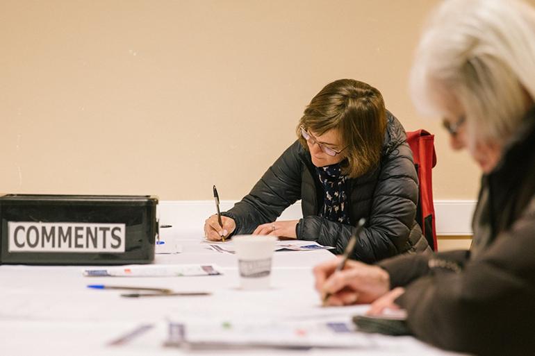 替换文本:  两个人坐在桌子旁填写意见提交表,桌子上放有贴上「意见 」标签的箱子。