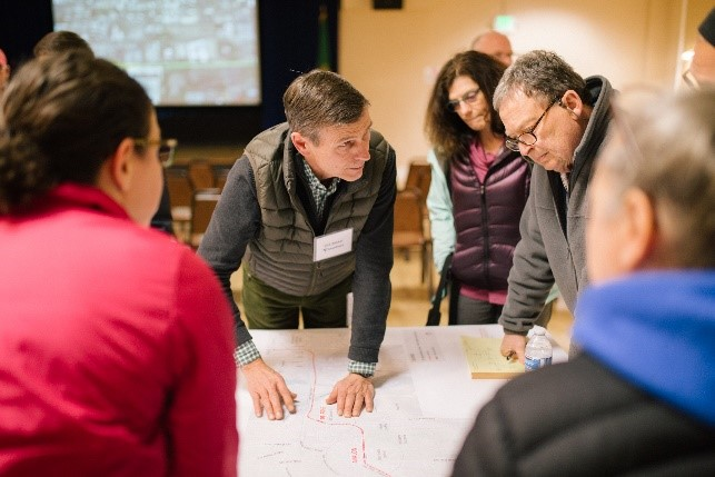 Photograph of a previous neighborhood forum, with community members looking at a project map with Sound Transit staff.