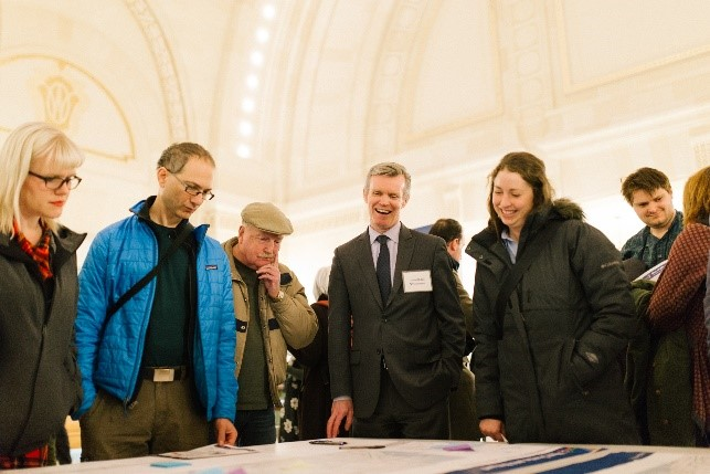 Photograph of community members looking at a project map with Sound Transit staff.